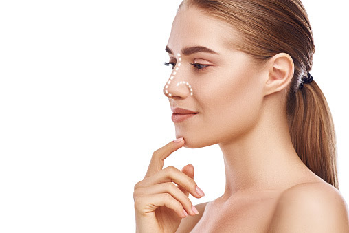 A beautiful woman touching her chin, dotted lines on her nose to indicate a potential rhinoplasty procedure.