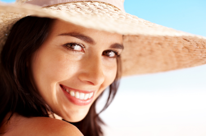 Beautiful smiling woman wearing a hat to protect her glowing, flawless skin